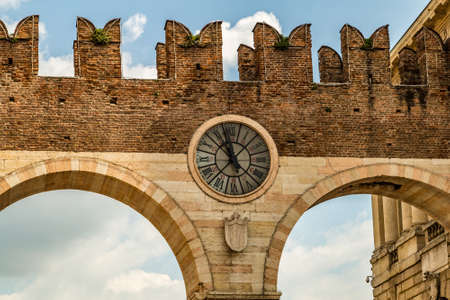 old clock placed on the top of the entrance city arched gate in Verona