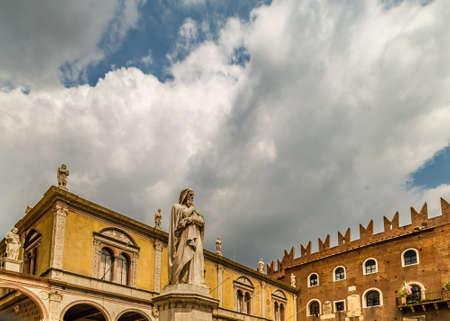 VERONA (VR), ITALY - MAY 10, 2019: sunlight is enlightening statue of Dante Alighieri holding his chin in Piazza dei Signori in Verona Banco de Imagens - 124648154
