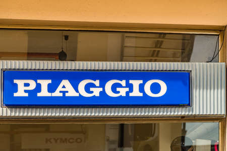 CERVIA (RA), ITALY - MAY 17, 2019: sunlight is enlightening Piaggio Logo on storefront in historical center of Cervia