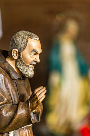 SAN BERNARDINO (RA), ITALY - MAY 20, 2019: sun is enlightening statue of Saint Father Pio waving his blessing hand with blurred statue of The Blessed Virgin Mary in background in Parish Catholic Church