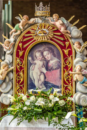 SAN BERNARDINO (RA), ITALY - MAY 20, 2019: sun is enlightening ancient picture of The Blessed Virgin Mary and Baby Jesus surrounded by statues of angels in Parish Catholic Church