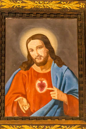 SAN BERNARDINO (RA), ITALY - MAY 20, 2019: sun is enlightening old picture of Jesus Christ pointing His Sacred Heart in Parish Catholic Church