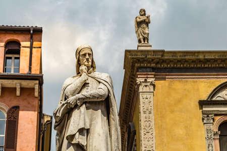 VERONA (VR), ITALY - MAY 10, 2019: sunlight is enlightening statue of Dante Alighieri holding his chin in Piazza dei Signori in Verona Banco de Imagens - 124660138