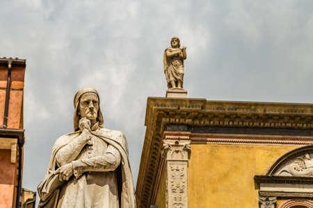 VERONA (VR), ITALY - MAY 10, 2019: sunlight is enlightening statue of Dante Alighieri holding his chin in Piazza dei Signori in Verona Banco de Imagens - 124660140