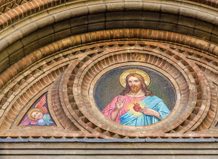 BOLOGNA, ITALY - MAY 10, 2019: sunlight is enlightening mosaic on facade of the Catholic Church of The Sacred Heart of Jesus in Bologna