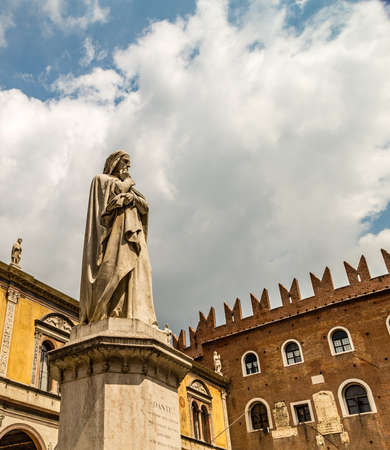 VERONA (VR), ITALY - MAY 10, 2019: sunlight is enlightening statue of Dante Alighieri holding his chin in Piazza dei Signori in Verona Banco de Imagens - 124660208