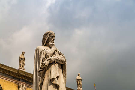 VERONA (VR), ITALY - MAY 10, 2019: sunlight is enlightening statue of Dante Alighieri holding his chin in Piazza dei Signori in Verona Banco de Imagens - 124660220