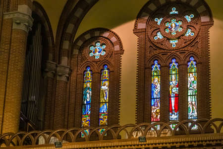 BOLOGNA, ITALY - MAY 10, 2019: sunlight is enlightening stained glasses of the Catholic Church of The Sacred Heart of Jesus in Bologna
