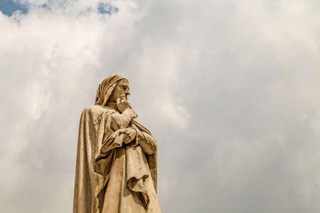 VERONA (VR), ITALY - MAY 10, 2019: sunlight is enlightening statue of Dante Alighieri holding his chin in Piazza dei Signori in Verona Banco de Imagens - 124660239