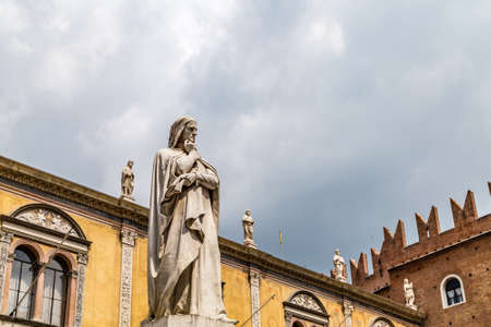 VERONA (VR), ITALY - MAY 10, 2019: sunlight is enlightening statue of Dante Alighieri holding his chin in Piazza dei Signori in Verona Banco de Imagens - 124660241