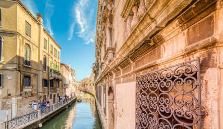 VENEZIA, ITALY – MAY 31, 2019: tourists visiting the city and enjoying the view of waters flowing in Rio Marin, water channel of Venice along Fondamenta Del Rio Marin