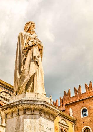 VERONA (VR), ITALY - MAY 10, 2019: sunlight is enlightening statue of Dante Alighieri holding his chin in Piazza dei Signori in Verona Banco de Imagens - 124660278