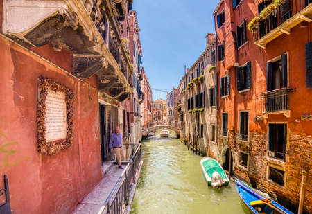 VENEZIA, ITALY – MAY 31, 2019: sunlight is enlighting a board reminding of the staying of Wolfgang Mozart in that house in Venice while boat passing in Rio dei Cuoridoro