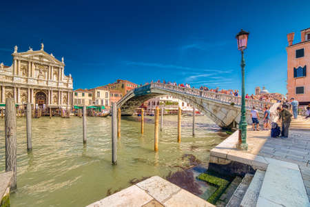 VENEZIA, ITALY – MAY 31, 2019: tourists visiting city while waters flowing in Canal Grande, main channel of Venezia, under Bridge Ponte degli Scalzi near Saint Mary of Nazareth church 新聞圖片