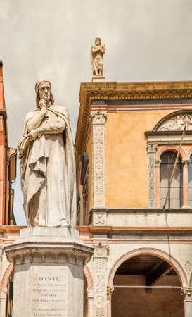 VERONA (VR), ITALY - MAY 10, 2019: sunlight is enlightening statue of Dante Alighieri holding his chin in Piazza dei Signori in Verona Banco de Imagens - 124660289