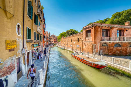 VENEZIA, ITALY – MAY 31, 2019: tourists visiting the city and enjoying the view of waters flowing in a Calle, typical street of Venice