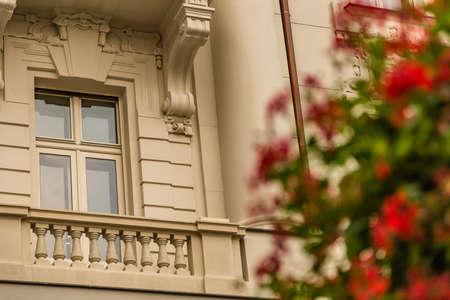 hanging red geraniums near ancient building Reklamní fotografie