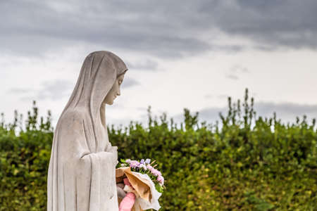 statue of The Blessd Virgin Mary holding flowers