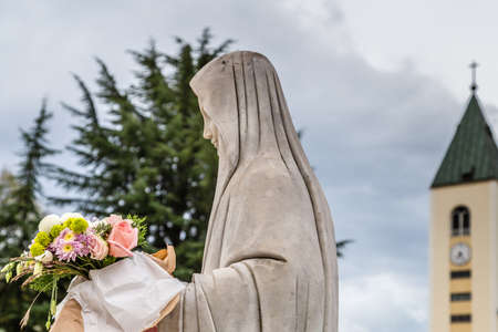 statue of The Blessd Virgin Mary holding flowers with church in background