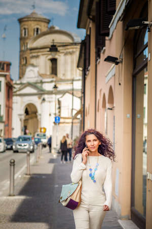 Classy woman wearing beige cream jumper and trousers and glass necklace walking in Ravenna, Italy talking on mobile phone