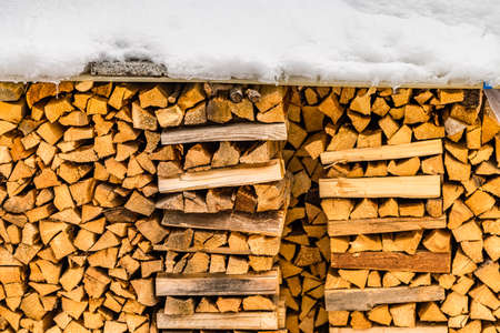 white snow covering stack of sawn wooden logs Italian mountains