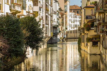 PADOVA, ITALY - FEBRUARY 23, 2019: sunlight is enlightening typical architecture of buildings on water channel in historical center in Padova