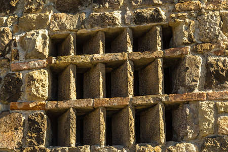 window with a grate of old bricks in ancient building Banco de Imagens