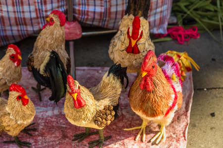 PADOVA, ITALY - FEBRUARY 23, 2019: sunlight is enlightening straw fake chickens for sale in market in Padua