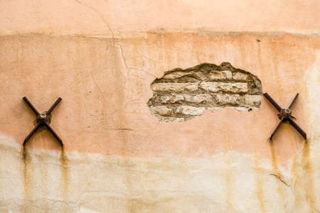 scraped wall of ancient building with rusty iron spikes of beams to stabilize the house