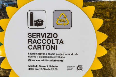 PADOVA, ITALY - FEBRUARY 23, 2019: sunlight is enlightening cardboard and paper collection service sign in historical center in Padova
