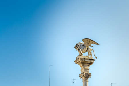 PADOVA, ITALY - FEBRUARY 23, 2019: sunlight is enlightening the statue of the winged lion of Saint Mark in Piazza dei SIgnori Editorial