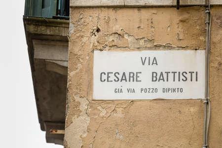 PADOVA, ITALY - FEBRUARY 23, 2019: sunlight is enlightening Cesare Battisti sign in historical center in Padova