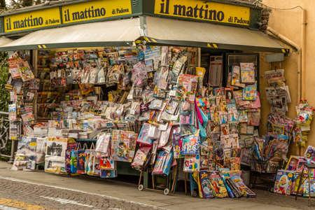 PADOVA, ITALY - FEBRUARY 23, 2019: sunlight is enlightening newspaper kiosk in market in Padua