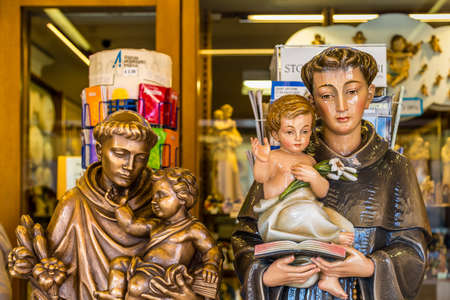 PADOVA, ITALY - FEBRUARY 23, 2019: sunlight is enlightening statues of Saint Anthony holding Baby Jesus for sale in souvenir shop