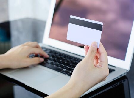 entering information: woman holding credit card in hand and entering information into a laptop, Shopping Online