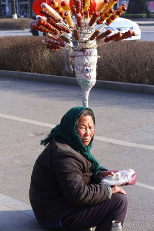 road side: old women selling sugar candy at road side Editorial