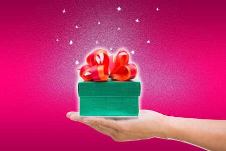 Green gift box with hand on pink background photo