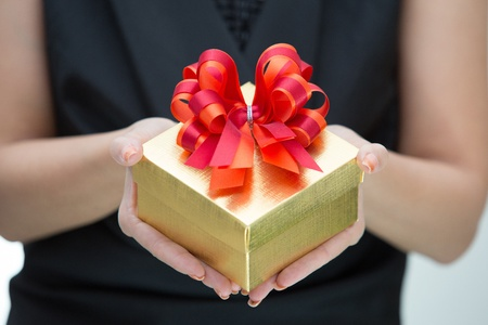 Golden gift box with red and orange satin bow on hand photo