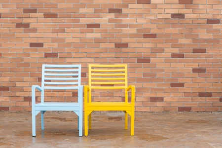 blue and yellow wooden chair and red brick wall  photo