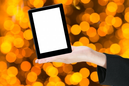 Hands with tablet computer. Isolated on yellow bokhe background. Stock Photo - 14917419