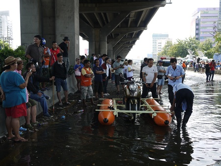 thailand flood: BANGKOK, THAILAND - NOVEMBER 07 - Thai flood hits Central of Thailand unidentified man try to make a raft for motorcycle - at Viphavadee-Rangsit rd. on November 07, 2011 in Bangkok, Thailand