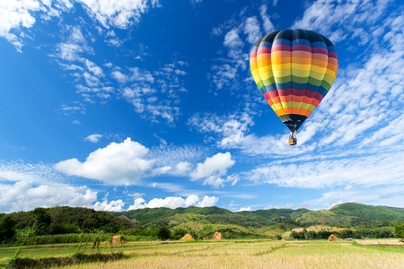 hot air balloon: Hot air balloon over the field with blue sky Stock Photo