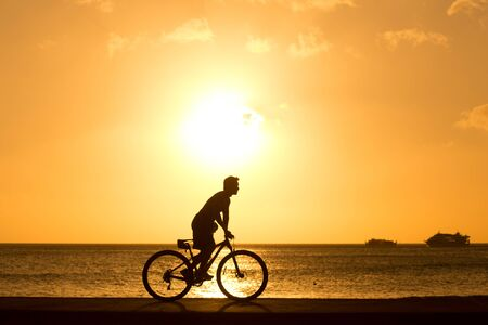 man ride bicycles outdoors against sunset. Silhouette.  photo