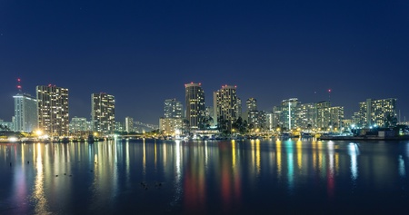 Honolulu downtown at night with seafront photo