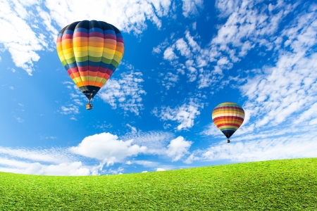 Colorful hot air balloon over green fields Stock Photo