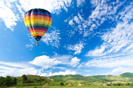 aeronautical: Colorful hot air balloon over green field Stock Photo