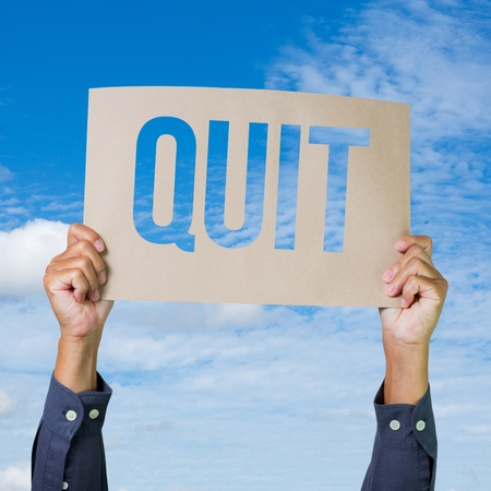 Two hands holding brown cardboard with quit overhead on blue sky background photo