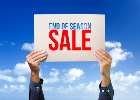cartel: Two hands holding brown cardboard with end of season sale overhead on blue sky background