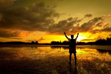 Silhouet van de mens met zijn handen omhoog kijken naar de zon