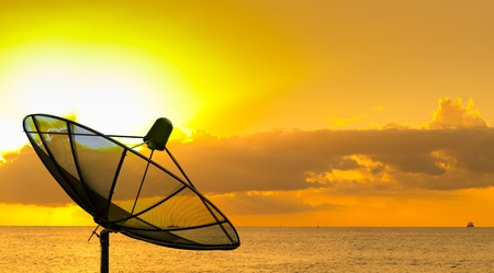 Side view of satellite dish with sunset photo